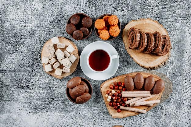 Alcuni tè con cialde e torte in piatti e tagliere su texture leggera