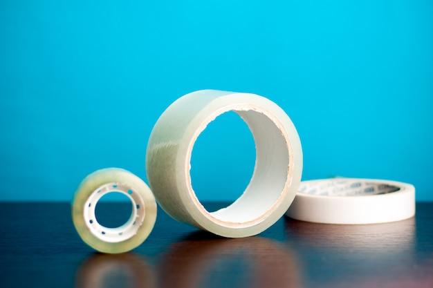 Alcuni tipi di adesivo di diverse dimensioni stanno su struttura di legno e sfondo blu