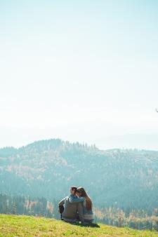 Alcuni viaggiatori di coppia ragazzi e ragazze che si siedono sulla scogliera rilassante vista aerea di montagne e nuvole amore e viaggi emozioni felici concetto di stile di vita.