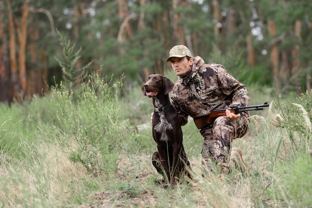 Alert hunter and dog in forest animal chasing.