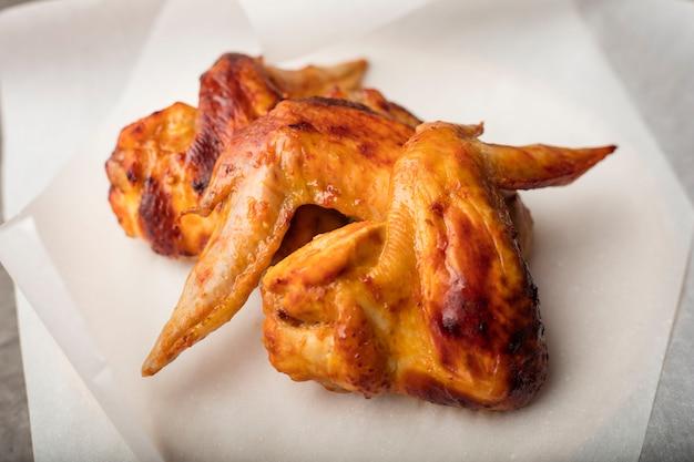 Alette di pollo fritte al barbecue. su carta alimentare bianca