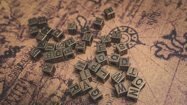 Alfabeti bronze d'annata sulla mappa di vecchio mondo