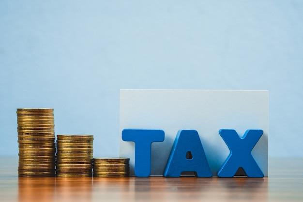 Alfabeto fiscale con pila di monete e biglietti da visita