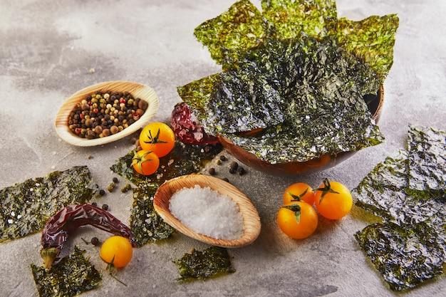 Alga croccante di nori con i pomodori ciliegia e le spezie in una ciotola di legno su calcestruzzo grigio. cibo giapponese nori. fogli secchi di alghe