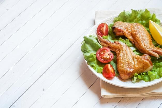 Ali di pollo affumicate con pomodoro e limone freschi della lattuga. copia spazio.