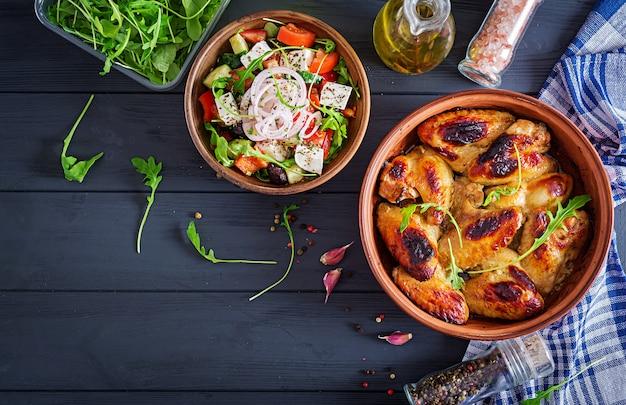 Ali di pollo al forno in ciotola sulla tavola di legno. vista dall'alto