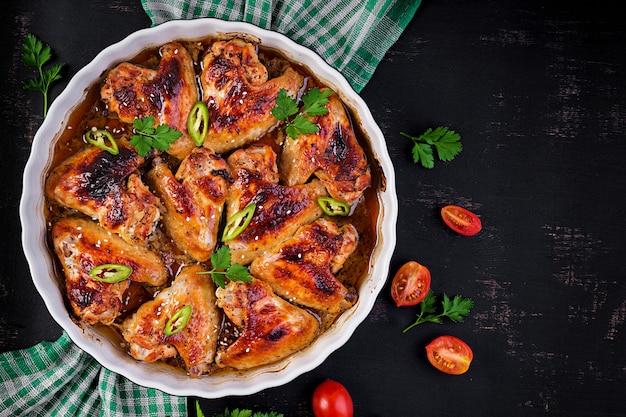 Ali di pollo al forno in stile asiatico sul piatto di cottura. vista dall'alto, dall'alto