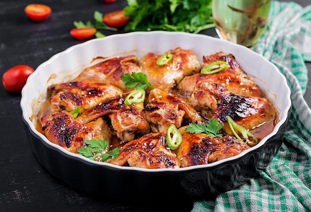 Ali di pollo al forno in stile asiatico sul piatto di cottura.