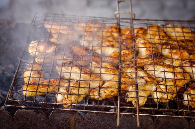 Ali di pollo alla griglia su una griglia con il fumo per la festa del cortile.