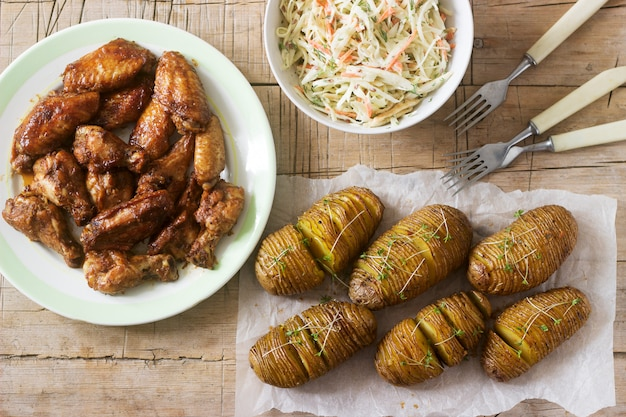 Ali di pollo americane, patate hasselback con salsa e insalata di cavolo su un fondo di legno. stile rustico.