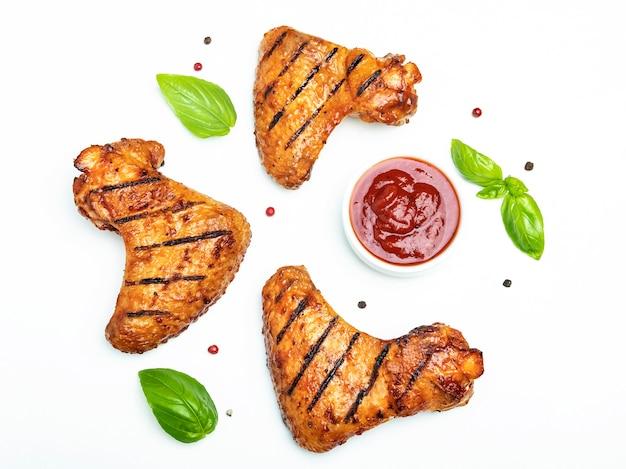 Ali di pollo arrostite, spezie rosse del basilico dei pomodori della salsa del bbq su bianco