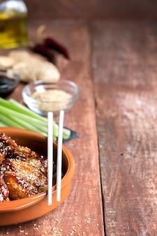 Ali di pollo asiatiche tradizionali della frittura di scalpore con sesamo e le verdure. copia