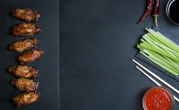 Ali di pollo asiatiche tradizionali della frittura di scalpore con sesamo e le verdure