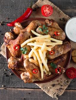 Ali di pollo con patatine fritte