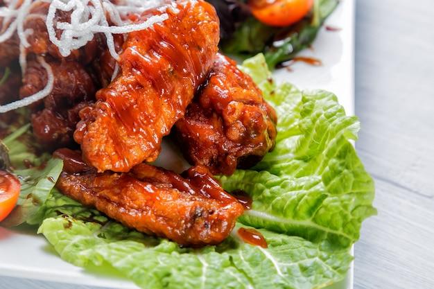 Ali di pollo con salsa barbecue, insalata, pomodori e patatine fritte sul piatto bianco