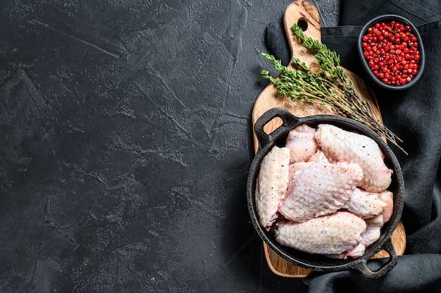 Ali di pollo crude con le spezie e le erbe in una pentola.