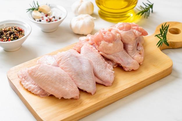 Ali di pollo crude fresche sul bordo di legno