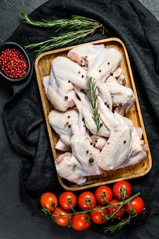 Ali di pollo crude in una ciotola di legno, cottura del rosmarino e del pepe rosa degli ingredienti, carne organica dell'azienda agricola, vista superiore.