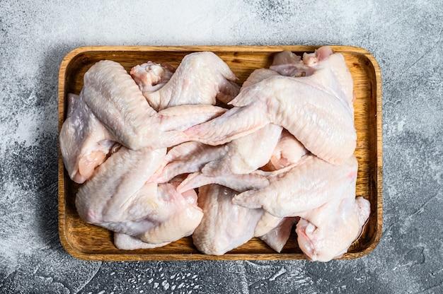Ali di pollo crude in una ciotola di legno, vista superiore