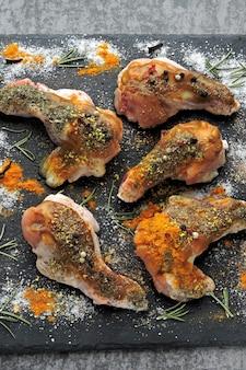 Ali di pollo crude marinate in spezie su un bordo di pietra nero.