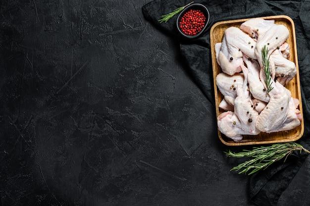 Ali di pollo crude, pollame organico dell'azienda agricola, vista superiore, spazio per testo