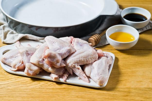 Ali di pollo crude su un bordo bianco ceramico.