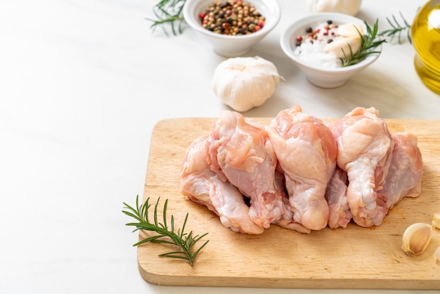 Ali di pollo fresche crude (drumette o bacchetta) su tavola di legno