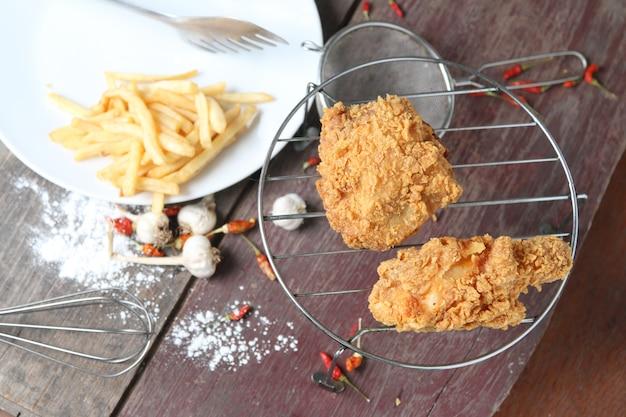 Ali di pollo fritto con le patate fritte sulla tavola di legno