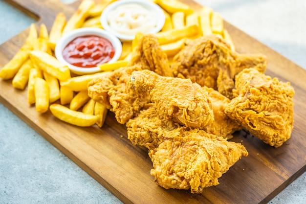 Ali di pollo fritto con patate fritte e pomodoro