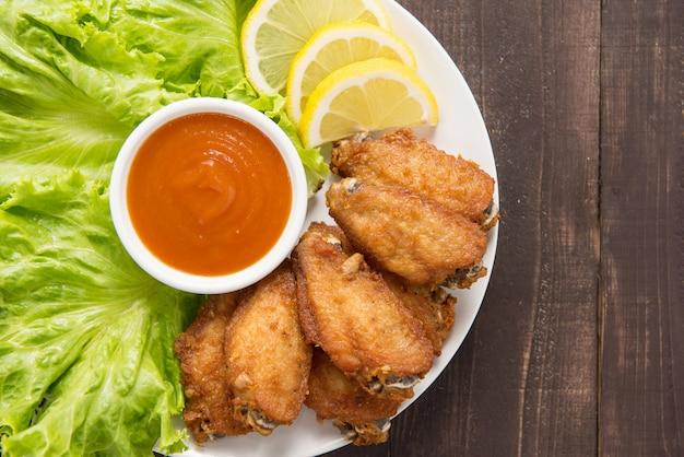 Ali di pollo fritto di vista superiore su fondo di legno