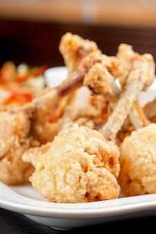 Ali di pollo fritto guarnite con verdure fresche con salsa teriyaki