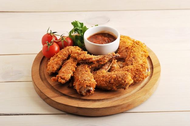 Ali di pollo fritto impanate con ketchup, pomodoro e prezzemolo