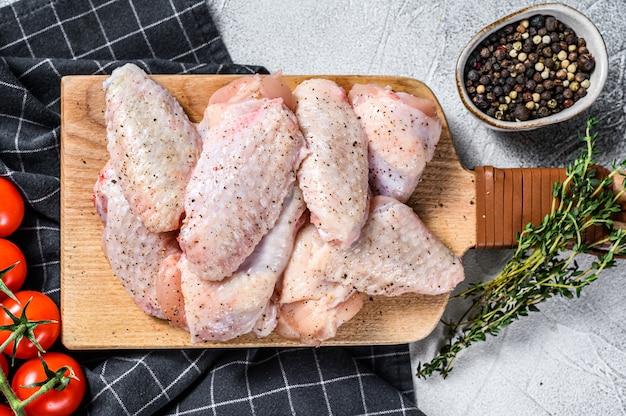 Ali di pollo grezze con spezie ed erbe aromatiche.