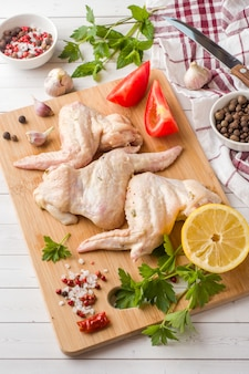 Ali di pollo grezze in marinata con salsa, pepe e verdure su w