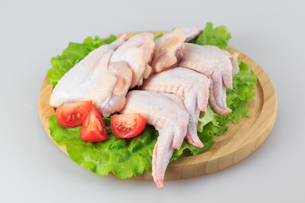 Ali di pollo grezze su bianco