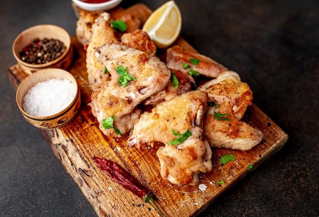 Ali di pollo grigliate in salsa barbecue con prezzemolo su un tagliere su un tavolo di cemento. vista dall'alto con spazio di copia.