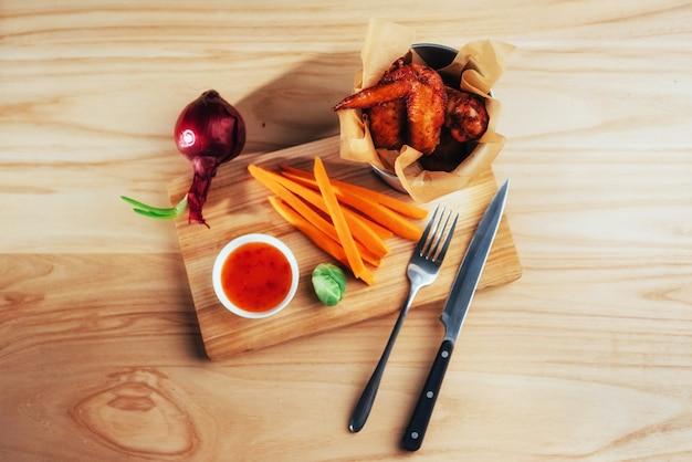 Ali di pollo guarnite con le verdure della salsa sulla tavola di legno