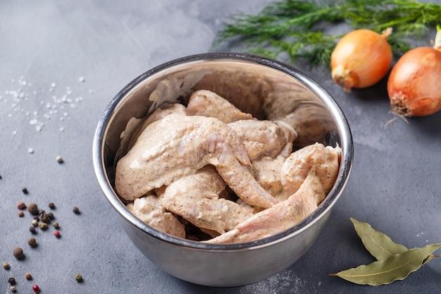 Ali di pollo marinate crude in una ciotola