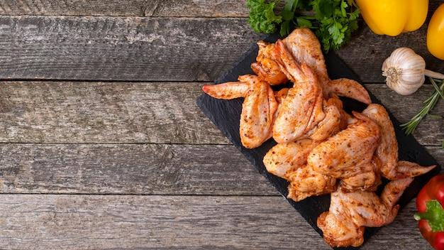 Ali di pollo marinate crude pronte da cucinare. . vista dall'alto