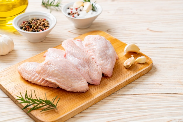 Ali di pollo medie crude fresche sul bordo di legno