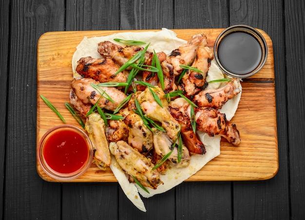 Ali e gambe di pollo su una tavola di legno
