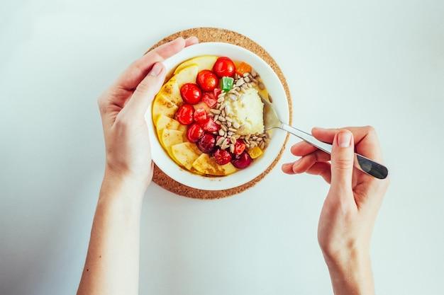 Alimentazione sana donna che mangia porridge con ciliegia, mela, frutti di candiet e semi di girasole