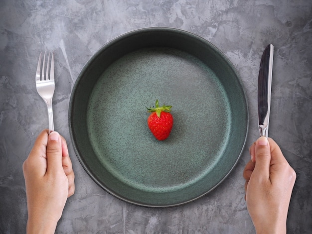 Alimentazione sana e perdita di peso con la frutta rossa della fragola sulla ciotola di ceramica verde con la mano con la forchetta e la lama.