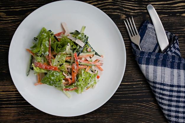 Alimenti dietetici, insalata di verdure fresche con imitazione di bastoncini di granchio, pezzi di carne, conditi con panna acida e sesamo giapponese