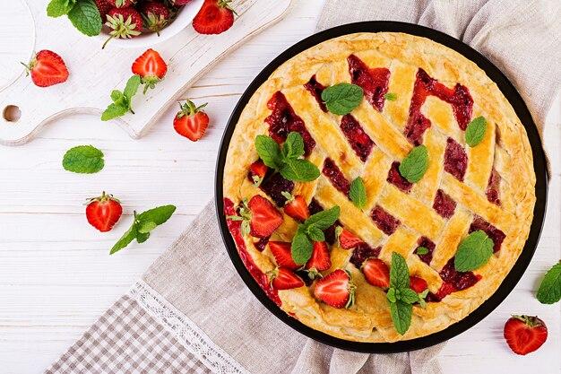 Alimento al forno dolce della pasticceria della torta crostata americana della torta della fragola sulla tavola di legno bianca, vista superiore
