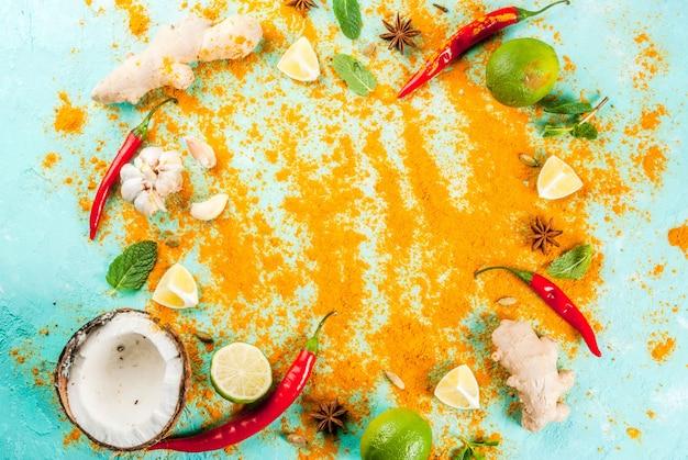 Alimento asiatico e tailandese che cucina fondo spezie ed ingredienti spezie calde della menta del curry dello zenzero dei peperoni dello zenzero della noce di cocco fondo blu-chiaro