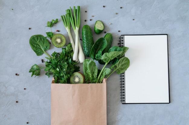 Alimento biologico verde differente in sacco di carta della drogheria con il taccuino in bianco aperto