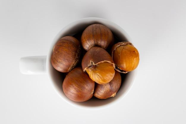 Alimento di autunno delle castagne in una tazza su bianco