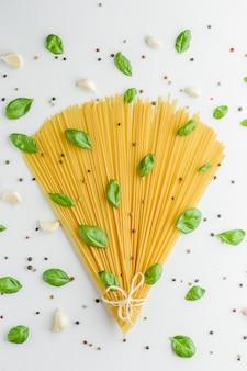 Alimento di concetto con pasta, basilico, aglio e pepe su bianco