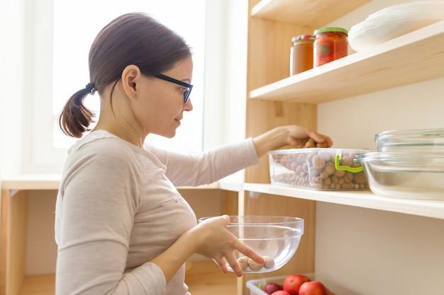 Alimento di raccolto della donna adulta dall'armadio di stoccaggio in cucina
